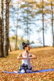 Молодая женщина делает упражнения йоги в осеннем городском парке. концепция здорового образа жизни.