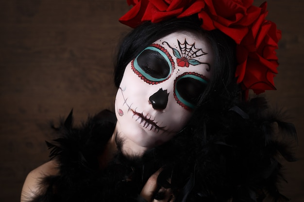 死霊のえじき。ハロウィン。死んだマスク頭蓋骨顔アートとバラの日の若い女性。暗い背景。