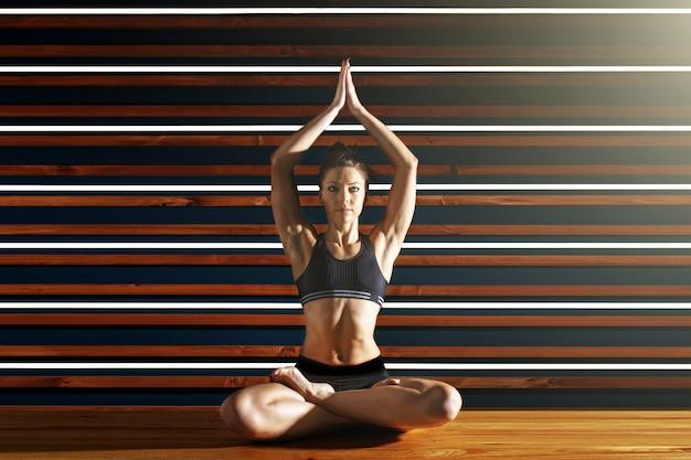 Молодая женщина делает упражнения йоги в темной студии. концепция здорового образа жизни.