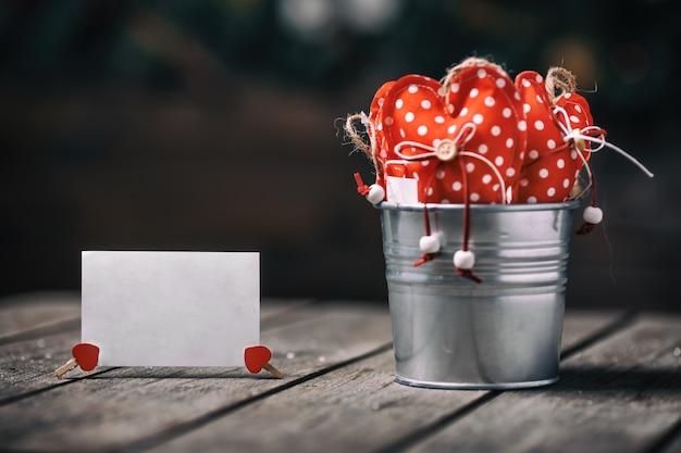 ヴィンテージとレトロなスタイルの紙のカードと木製の背景に亜鉛バケツに赤いハート。バレンタインのコンセプト。