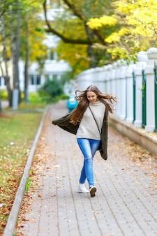秋の公園を歩いてフード付きの緑のニットカーディガンの美しい若い女性