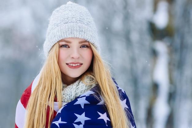Портрет зимы девушки подростка с флагом сша. красотка радостная модель девушка смеяться и веселиться в зимнем парке
