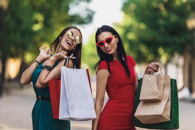 夏の街で買い物袋を持つ若い魅力的な女の子。カメラ目線と笑顔のサングラスの美しい女性。肯定的な感情とショッピングの日の概念。
