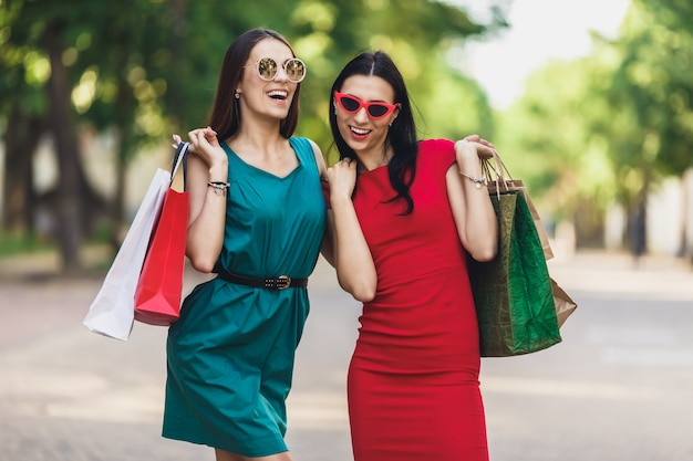 Молодые привлекательные девушки с сумки в городе летом. красивые женщины в солнцезащитные очки, глядя на камеру и улыбается. положительные эмоции и концепция торгового дня.