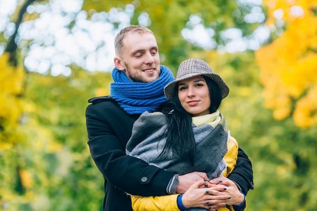 秋の公園の若者。黄色の木と葉。幸せな若い家族の概念。