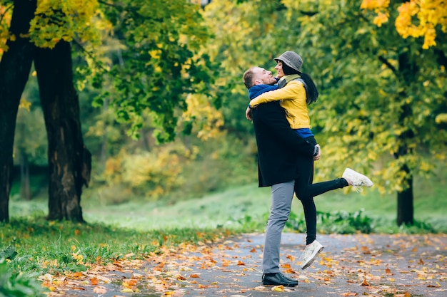 秋の公園で楽しんで幸せなカップル。黄色の木と葉。屋外の男と女を笑っています。自由の概念。