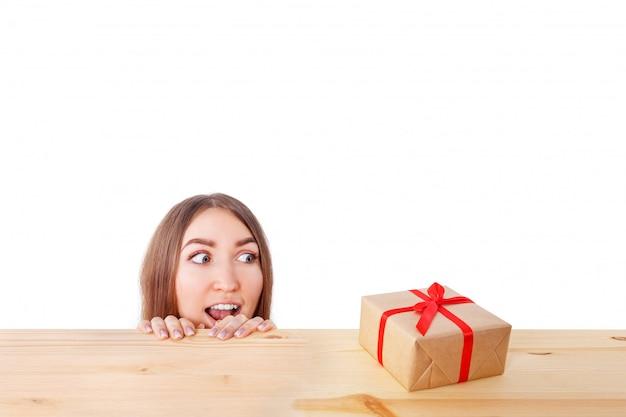 Удивленная женщина смотрит на подарочную коробку. рождество, рождество, зима, понятие счастья.