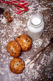 Домашнее овсяное печенье с орехами, изюмом, конфетами и бутылкой молока на темном деревянном фоне