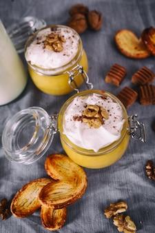 ホイップクリーム、タフィー、クルミ、蜂蜜のクッキーとガラスの瓶にカボチャのミルクセーキ