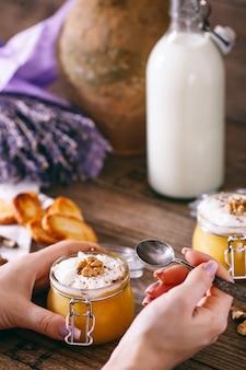 スプーンで女性の手。ホイップクリーム、タフィー、クルミ、蜂蜜のクッキーとガラスの瓶にカボチャのミルクセーキ