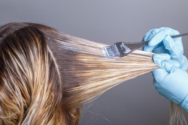 サロンで彼女のクライアントの髪を染めるプロの美容師