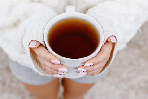 お茶のカップを保持している女性