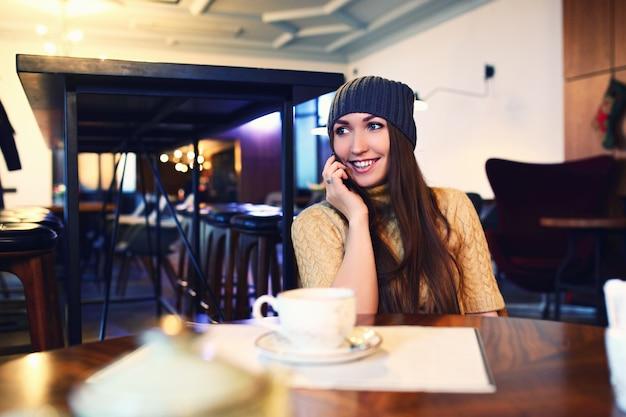 Портрет красивой девушки в шляпе, используя ее мобильный телефон в кафе