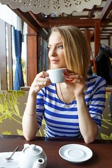 Красивая молодая девушка отдыхает в кафе и смотрит в окно