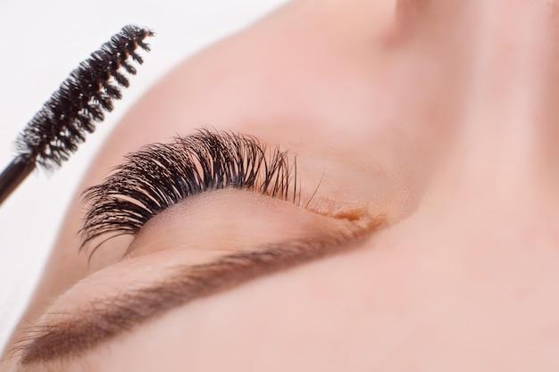 Процедура наращивания ресниц. женский глаз с длинными ресницами