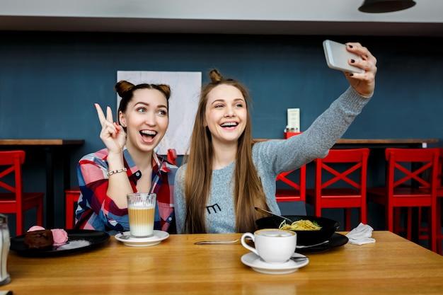 Две молодые красивые женщины-хипстеры, сидящие в кафе, стильный модный наряд, европейские каникулы, уличный стиль, счастливые, веселиться, улыбаться, солнцезащитные очки, смотреть на смартфон, делать селфи фото, кокетливый