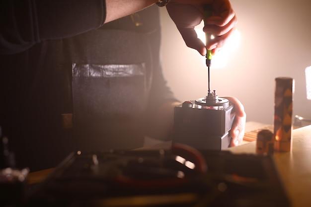 タバコを吸うための電子タバコのアトマイザーデッキベースで新しいデュアルコイルの燃焼をテストし、シーンをクローズアップ