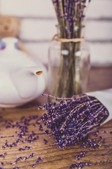 Куча сухой вырезать лаванды и чайник на деревянный стол. белые кирпичи.