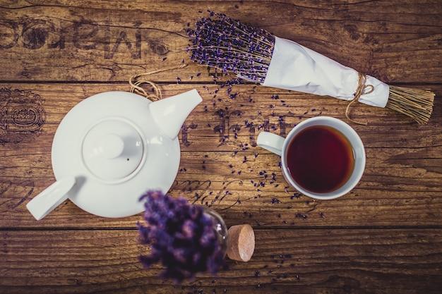 Куча сухой нарезанной лаванды, чашка чая и чайник на деревянный стол. вид сверху.