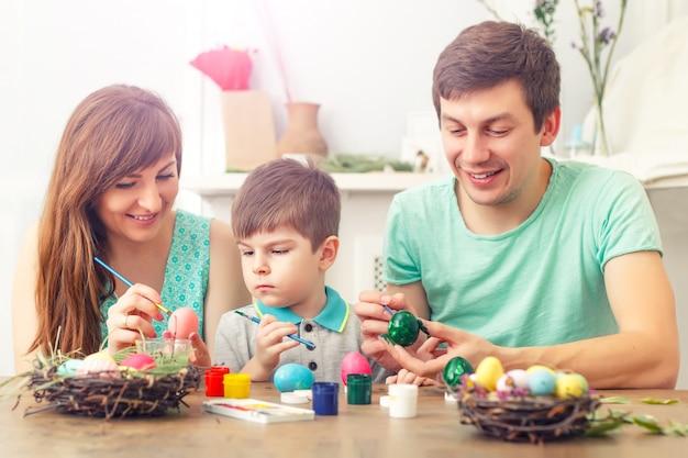 母、父、息子は卵を描いています。幸せな家族がイースターの準備をしています。