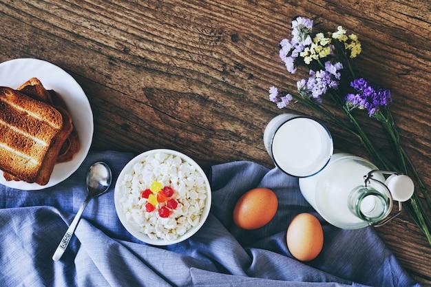 Молочные продукты на темном деревянном столе. сметана, молоко, сыр, яйцо и тосты. вид сверху с копией пространства