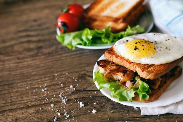Бутерброд с яйцом, курицей, огурцом и салатом на деревянном фоне копией пространства