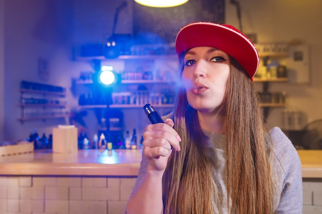 赤い帽子の若いきれいな女性がアークショップで電子タバコを吸う