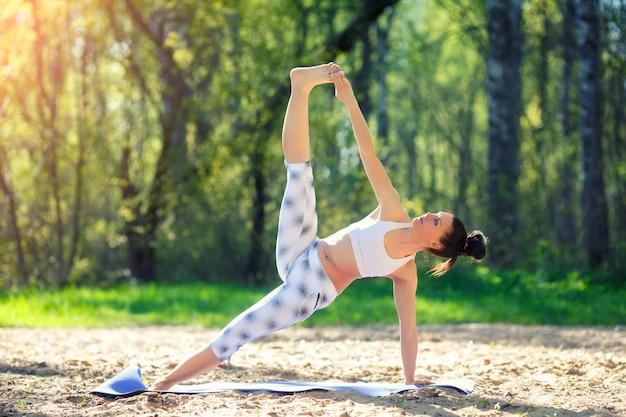 Молодая женщина делает упражнения йоги в городском парке летом