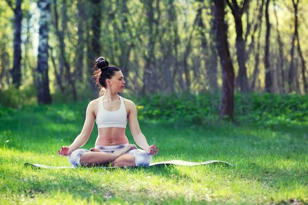 夏の都市公園でヨガの練習を行う若い女性