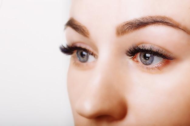 まつげエクステンション手順。長いまつげの女性の目
