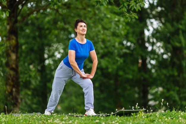 公園で運動する年配の女性。