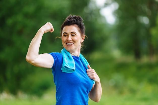 公園で屋外の筋肉がうごめく年配の女性の笑みを浮かべてください。上腕二頭筋を示す高齢者の女性