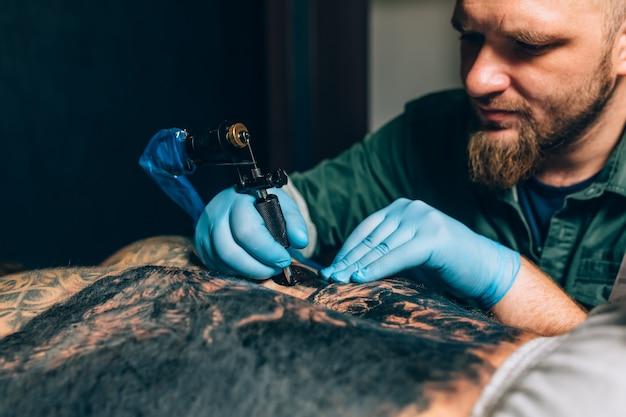 タトゥーマスターアーティストは、タトゥーを作ります。閉じる
