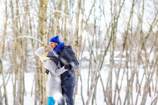 笑って、楽しんで冬の公園で幸せな若いカップル。家族のアウトドア。