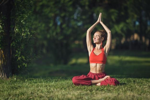若い女性が屋外でヨガを練習します。女性は夏の都市公園で屋外で瞑想します。