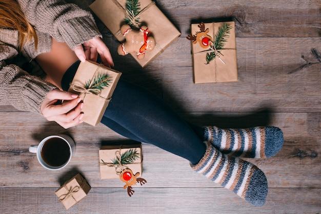 床に座って女性がプレゼントをラッピングし、クリスマスの時にコーヒーを飲む