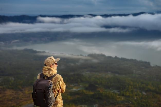 Турист человек смотрит на восход солнца на вулкан батур на острове блай в индонезии. турист человек с рюкзаком путешествия на вершине вулкана, концепция путешествия