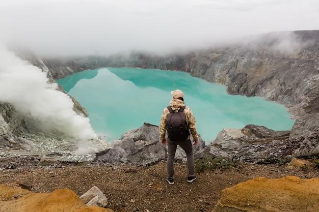 男性観光客は、インドネシアのジャワ島のイジェン火山の硫黄湖を見ています。ハイカーのバックパックを持つ男旅行トップマウンテン、旅行の概念