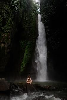 Красивая молодая женщина, медитируя в позе лотоса, занимаясь йогой в прекрасном лесу возле водопада. красивая женщина практикующих йогу на скале у тропического водопада