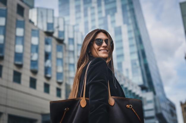 通りを歩いてサングラスの美しいスタイリッシュな少女。女性の肖像画を間近にカメラと笑顔で好転します。