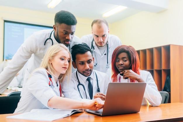 Многорасовая команда молодых врачей, работающих на портативный компьютер в медицинский офис.