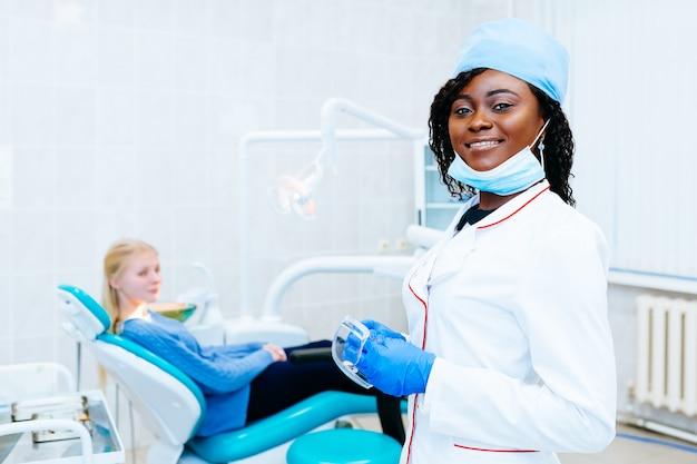 Молодой усмехаясь афро-американский женский дантист перед пациентом на клинике. концепция стоматологической клиники.