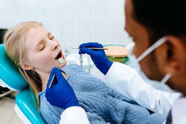 Молодой уверенно азиатских мужчин стоматолог лечение женского пациента в клинике. концепция стоматологической клиники.