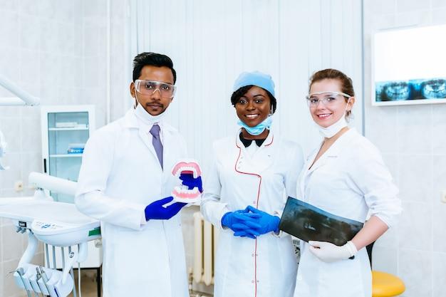 Многорасовая стоматологическая бригада. стоматолог держать челюсть модель, рентген, улыбается и смотрит на камеру. концепция стоматологического здоровья.