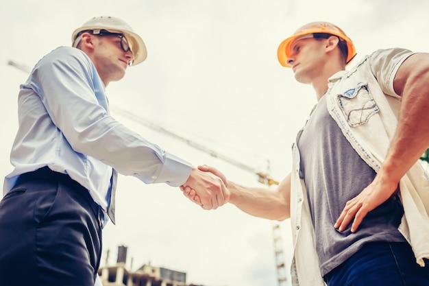 Архитектор инженер рукопожатие другой стороны на строительной площадке. бизнес коллективная работа, сотрудничество, концепция успеха сотрудничества