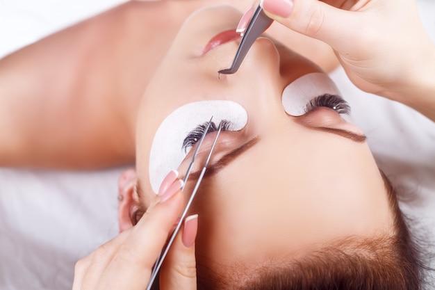 Процедура наращивания ресниц. женский глаз с длинными ресницами. ресницы со стразами. ресницы, крупный план