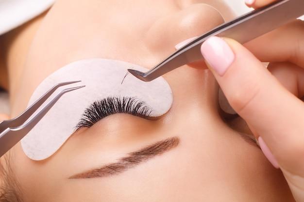 Процедура наращивания ресниц. женский глаз с длинными ресницами.