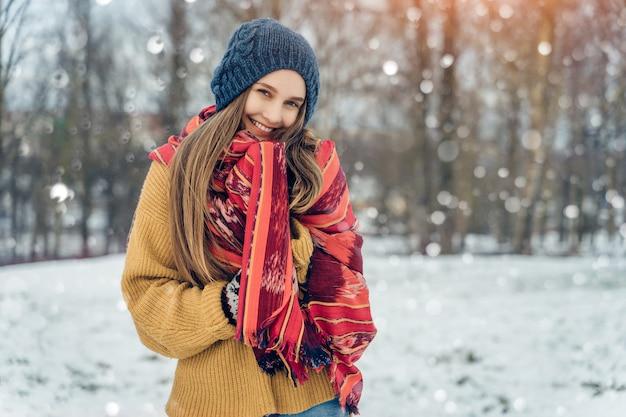 冬の若い女性の肖像画。笑って、冬の公園で楽しんでうれしそうな美少女モデル。美しい若い女性屋外、自然を楽しんで、冬