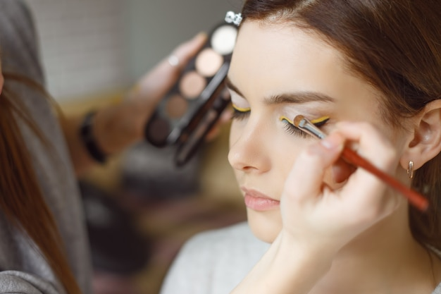 サロンでモデルに化粧を適用する若い女性
