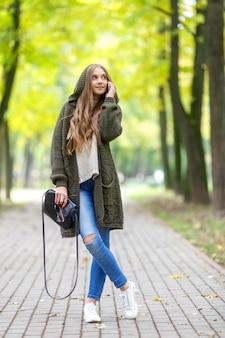 秋の公園を歩いて、携帯電話を話しているフード付きの緑のカーディガンの美しい若い女性。